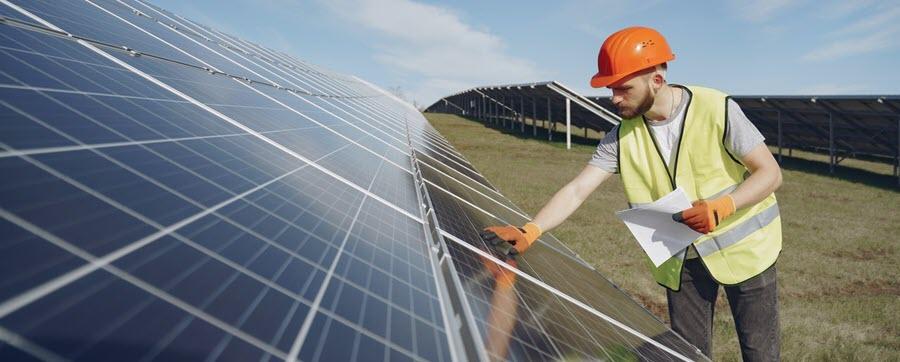 worker inspecting solar panels
